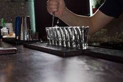 Barman pouring liquor into shot glasses Stock Photos