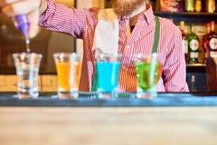 Barman Pouring Liquor Shots images stock