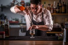 Barman pouring mixture into a jigger Royalty Free Stock Photography