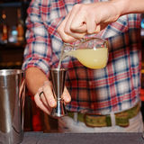 Barman is pouring orange jucie in jigger Stock Photos