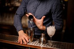 Barman pouring a portion of vodka into the shaker Stock Images