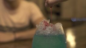 Barman pouring red liquor on ice while making alcoholic cocktail at bar counter in pub. Close up bartender making. Cocktail with ice and color liquor in glass stock footage