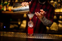 Barman pouring red sweet juicy drink into a cocktail glass. Using a shaker and strainer royalty free stock photos