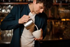 Barman pouring some milk from pitcher into a cup. Young curly barman pouring some milk from pitcher into a little white cup in a restaurant Stock Photography
