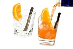 Barman pouring spritz aperitif aperol cocktail in two glasses with orange slices and ice cubes Stock Images
