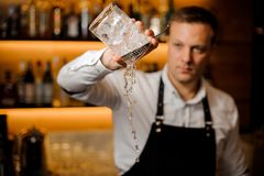 Barman pouring water from a glass with ice cubes stock photo