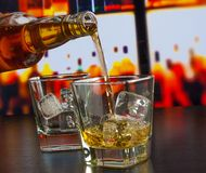 Barman pouring whiskey on bar table Royalty Free Stock Photography