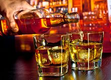 Barman pouring whiskey on bar table Royalty Free Stock Photos