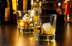Barman pouring whiskey behind whiskey glass Royalty Free Stock Photo