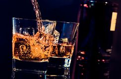 Barman pouring whiskey in front of whiskey glass and bottle Royalty Free Stock Images