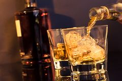 Barman pouring whiskey in front of whiskey glass and bottle Royalty Free Stock Image