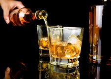 Barman pouring whiskey in front of whiskey glass and bottles Stock Image