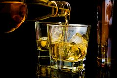 Barman pouring whiskey in front of whiskey glass and bottles Stock Photo