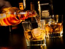 Barman pouring whiskey in front of whiskey glass and bottles. On wood table Royalty Free Stock Images