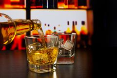 Barman pouring whiskey in front of whiskey glass and bottles. On wood table Royalty Free Stock Image