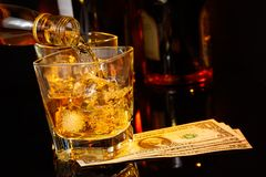 Barman pouring whiskey in front of whisky glass and bottles near dollars Stock Image