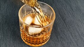 Barman pouring whiskey in the glass with ice cubes on table, focus on ice cubes, whisky relax time on warm