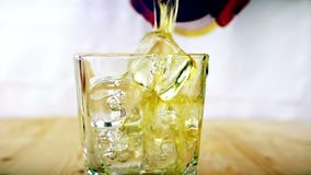 Barman pouring whiskey in the glass with ice cubes on wood table background, focus on ice cubes, whisky relax time, gold warm stock footage