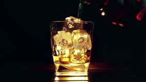 Barman pouring whiskey in the glass with ice cubes on wood table and black dark background, focus on ice cubes, whisky relax time stock video