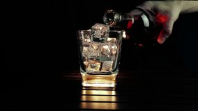 Barman pouring whiskey in the glass with ice cubes on wood table and black dark background, focus on ice cubes, whisky relax time stock footage