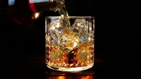 Barman pouring whiskey in the glass with ice cubes on wood table and black dark background, focus on ice cubes, whisky relax stock video