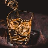 Barman pouring whiskey in the glass on wood table, warm atmosphere, old style, time of relax with whisky Stock Image