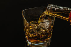 Barman pouring whiskey with ice cubes in glass on black background, cool atmosphere Stock Photos