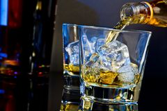 Barman pouring whiskey in two glasses with ice cubes on table with light tint blue and reflection Stock Image