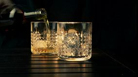 Barman pouring whiskey in the two glasses with ice cubes on wood table and black dark background, focus on ice cubes, whisky stock video footage
