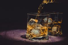 Barman pouring whiskey in two glasses on wood table, warm atmosphere, old style, time of relax with whisky Stock Photo