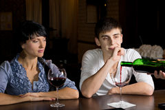 Barman pouring wine watched by a young couple Stock Images