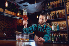 The barman pours alcohol into a glass.  Stock Photography