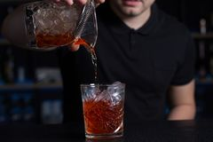 Barman pours alcohol or juice into a glass over ice. royalty free stock photo
