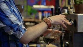 Barman pours beer into a glass from the beer tap in the pub. Bartender services the guest in cafe. Close-up stock video