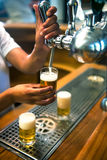 Barman pours beer into glasses Royalty Free Stock Photos
