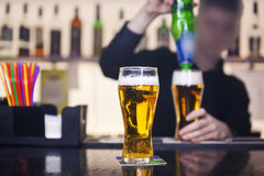 The barman pours a glass of beer in the pub Stock Images