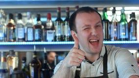 Barman pozycja przy odpierający ono uśmiecha się pokazywać jego kciuk up Fotografia Stock