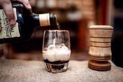 Barman préparant et versant la boisson alcoolisée dans le verre de cocktail Image libre de droits