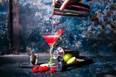 Barman préparant et versant le cocktail rouge dans la classe de marini cocktail cosmopolite sur le fond en métal Photos libres de droits