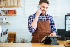 Barman prenant l'ordre sur le téléphone portable et à l'aide du comprimé dans le cafétéria Photo libre de droits