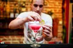 Barman preparing cosmopolitan alcoholic cocktail drink at bar. Alcoholic drink with vodka, triple sec, cranberry juice and lemon juice stock images