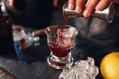 Barman preparing fresh negroni cocktail. Close up shot of bartender hand pouring drink from measuring cup into a cocktail glass filled with ice cubes. Barman Royalty Free Stock Photography