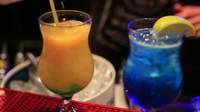 Barman preparing two colorful exotic cocktails in night club stock video