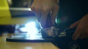 Barman pressant le café avec la presse spéciale Support de filtre dans des mains femelles banque de vidéos