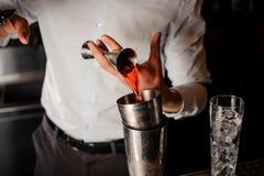 Barman professionnel ajoutant une boisson alcoolisée rouge transparente dans le dispositif trembleur en acier Photo libre de droits