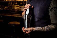 Barman professionnel tenant le dispositif trembleur de cocktail en acier Image stock