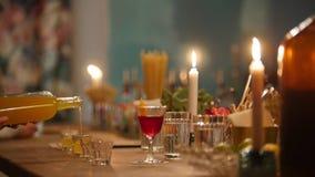 Barman professionnel versant l'orangeade dans de petits verres dans la barre avec l'éclairage intérieur doux photos stock