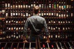 Barman przy wino lochem pełno butelki z wyśmienitymi napojami obrazy stock