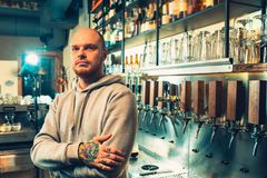 Barman in a pub near beer taps. See in the camera. Glasses on the bar shelf. Man with tattoo. Pub. Grey hoody. Bald man. Beer bar concept Royalty Free Stock Photos