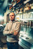 Barman in a pub near beer taps. See in the camera. Glasses on the bar shelf. Man with tattoo. Pub. Grey hoody. Bald man. Beer bar concept Stock Image